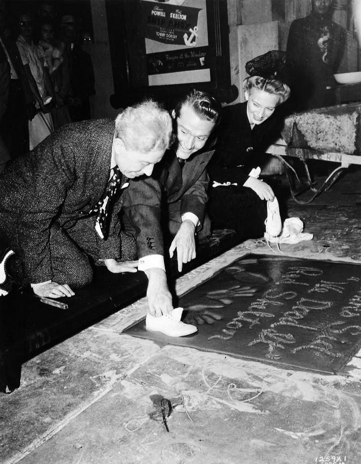 "Photo of Red and Edna Skelton and Sid Grauman at Skelton's imprint ceremony at Grauman's Chinese Theater. Skelton is shown making a print with his character, ""Junior's"" shoes in addition to his own and his handprints. The inscription reads, ""Thanks, Sid We Dood it!"" (signed Red Skelton)."