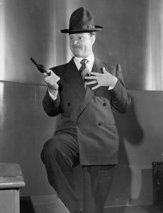 Red Skelton holding a gun on the studio audience during his monologue