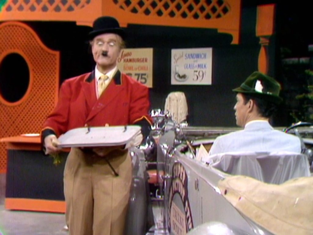 Car hop Red Skelton, impersonating Charlie Chaplin, trying to impress the talent agent.