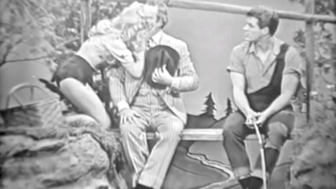 Daisy Mae kisses Clem while Li'l Abner watches