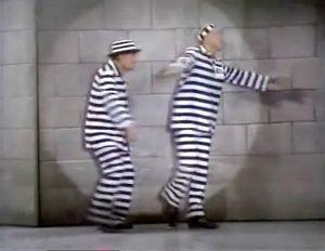 Bolivar Shagnasty (Red Skelton) and Butch (Cesar Romero) dancing in the prison spotlight