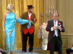 Freddie at the fashion show, unravelling the model in the saran, as Horace (Terry-Thomas) watches