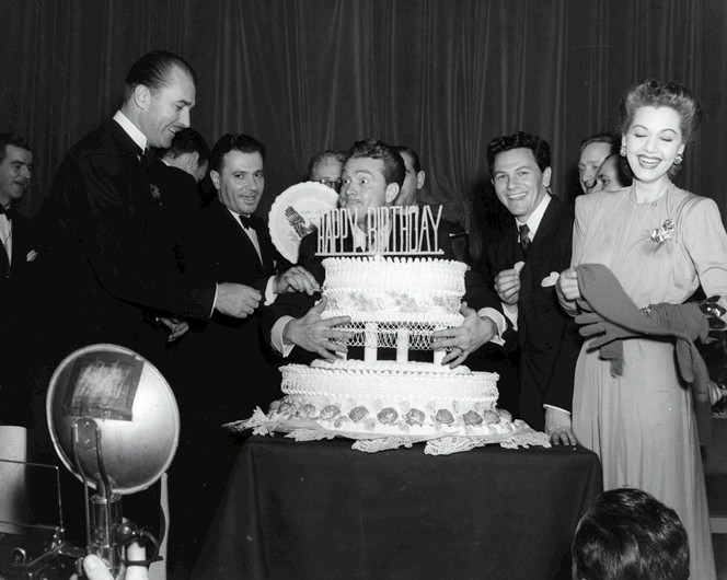 Photo of Red Skelton and John Garfield at Franklin D. Roosevelt's Birthday Ball in 1944. Skelton served as the master of ceremonies for FDR's official birthday celebration for many years. It's now time to cut the cake, but Red has decided to keep it all for himself.