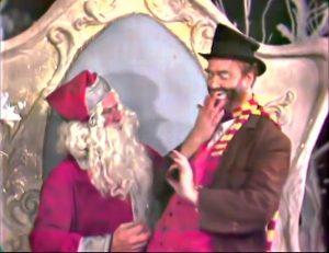 """Freddie the Freeloader sitting on Santa's lap in """"Freddie and the Yuletide Doll"""""""