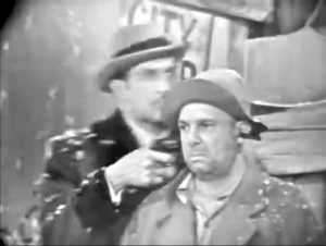 Gilbert (Vincent Price) comedically holds a gun to Muggsy's (Jackie Coogan) heads -- and straight through it!