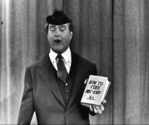 """Clem Kadiddlehopper trying to sell a book about hiccups in The Red Skelton Show episode, """"The Railroad Station"""""""