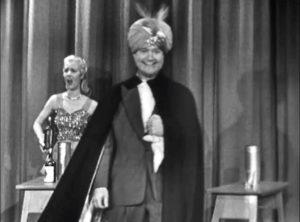 J. Newton Numbskull - magician triumphant, despite assistant Lucille Knoch attempting to sabotage his trick