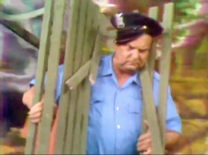 """Police officer (Jackie Coogan) unintentionally hit by Freddie's park bench in """"Hippie Days are Here Again"""""""