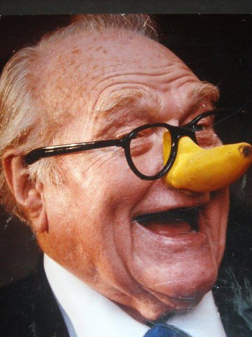 Older Red Skelton wearing a banana nose