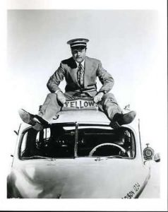 Publicity photo for The Yellow Cab Man - Red Skelton sitting on top of a yellow cab